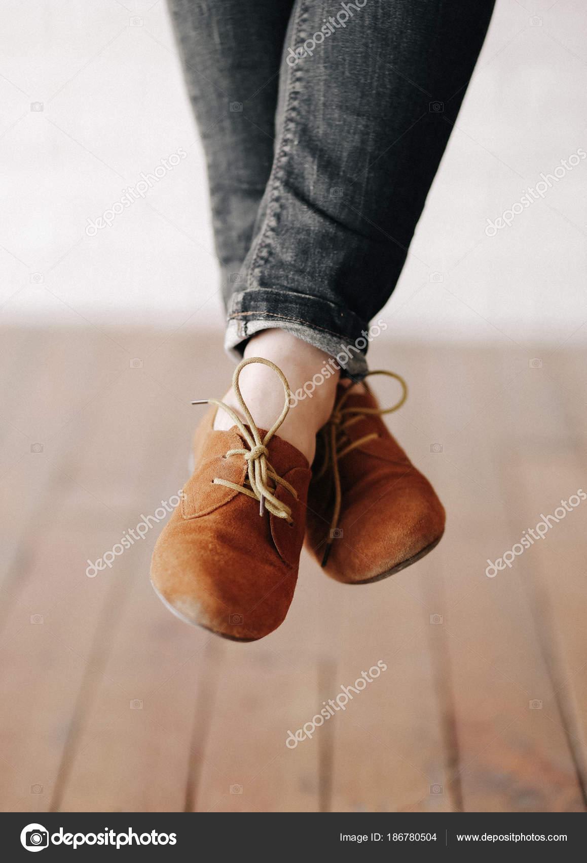 3a3f960c5545 Γυναικεία πόδια σε παπούτσια με κορδόνια που δεν αγγίζουν το πάτωμα —  Εικόνα από ...