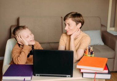 Mother teaches child son at home with laptop online education