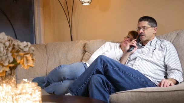 Man uses Voice Activated remote control while on couch watching TV with wife