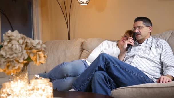 Man uses Voice Activated remote control while on couch watching TV with wife ALT