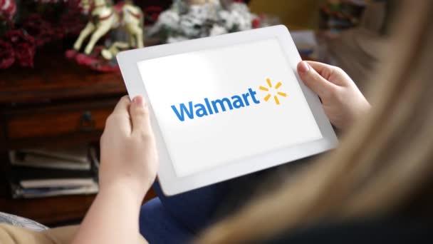 Ženy při pohledu na Walmart logo na tabletu pouze pro redakční použití. Komerční využití tohoto klipu je zakázáno