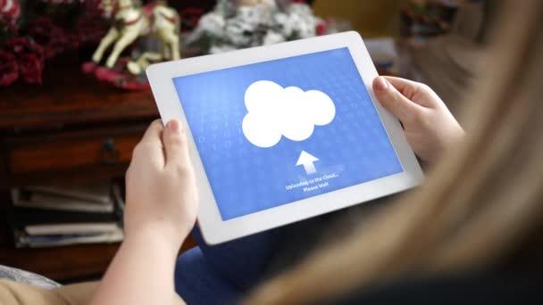 Žena používá tabletu předávat soubory do cloudu v rustikální obývací pokoje