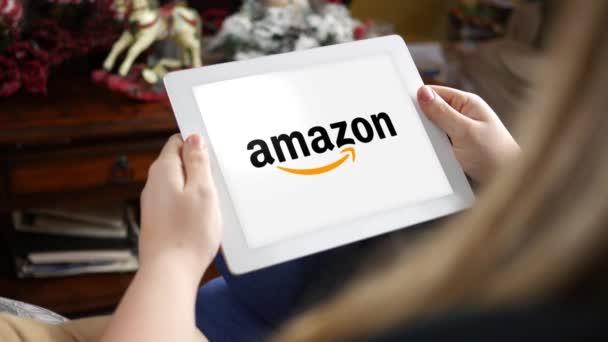 Ženy při pohledu na Amazon logo na tabletu pouze pro redakční použití. Komerční využití tohoto klipu je zakázáno