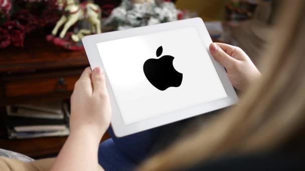 Ženy při pohledu na Apple logo na tabletu pouze pro redakční použití. Komerční využití tohoto klipu je zakázáno