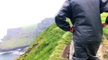 POV following man to the Cliffs of Moher in Ireland