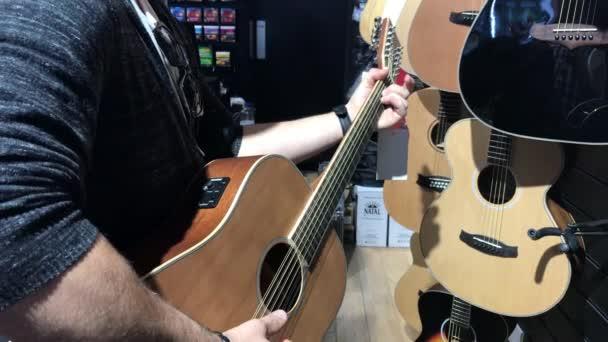 Irsko - cca června 2017 - muž hraje na kytaru v obchodě s hudebninami v Irsku