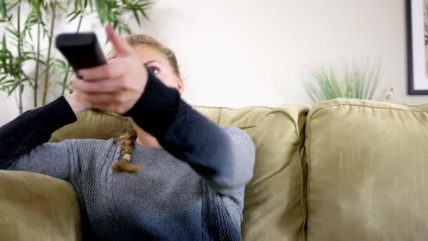 Mladá žena uvolňuje ve svém obývacím pokoji a čumí na televizi