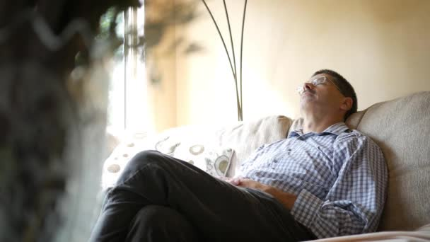 Middle Aged Caucasian male taking a nap on a couch during the day