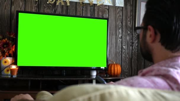 Znuděný tisícileté mužské kanál surfování na zelené obrazovce Tv s dálkovým ovládáním