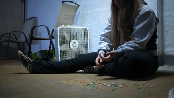 eine Frau nimmt eine Pille aus dem Boden und schluckt sie in einem Trap House - alt