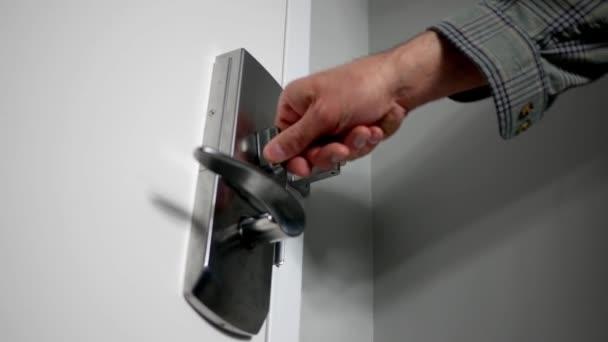 Muž chrom kovové zamykání zamkne ve svém domě