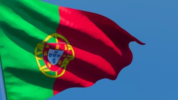 Portugália nemzeti zászlaja a szélben repül a kék ég felé.