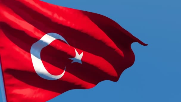 Národní vlajka Turecka vlaje ve větru proti modré obloze