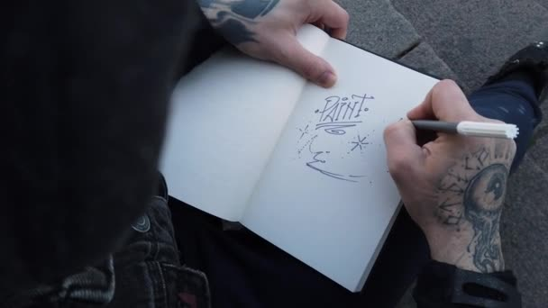male hands in tattoos draw in a sketchbook