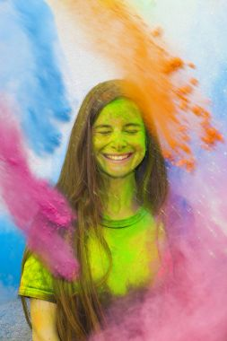 Young cheerful girl under explosion of colored powder at Holi colors (paints) party. Freeze motion (stop motion) of color powder exploding or throwing colour powder. Multicolored glitter explosion.