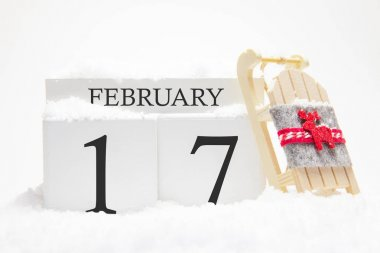 Wooden calendar for February, 17 th day of the winter month. The symbols of winter are snow and sleigh. Concept of holidays, vacation and winter fun.