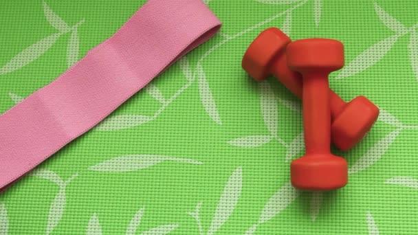 Pomerančové činky na zeleném sportovním koberci. Dívka klade sportovní gumičky a láhev pro woter