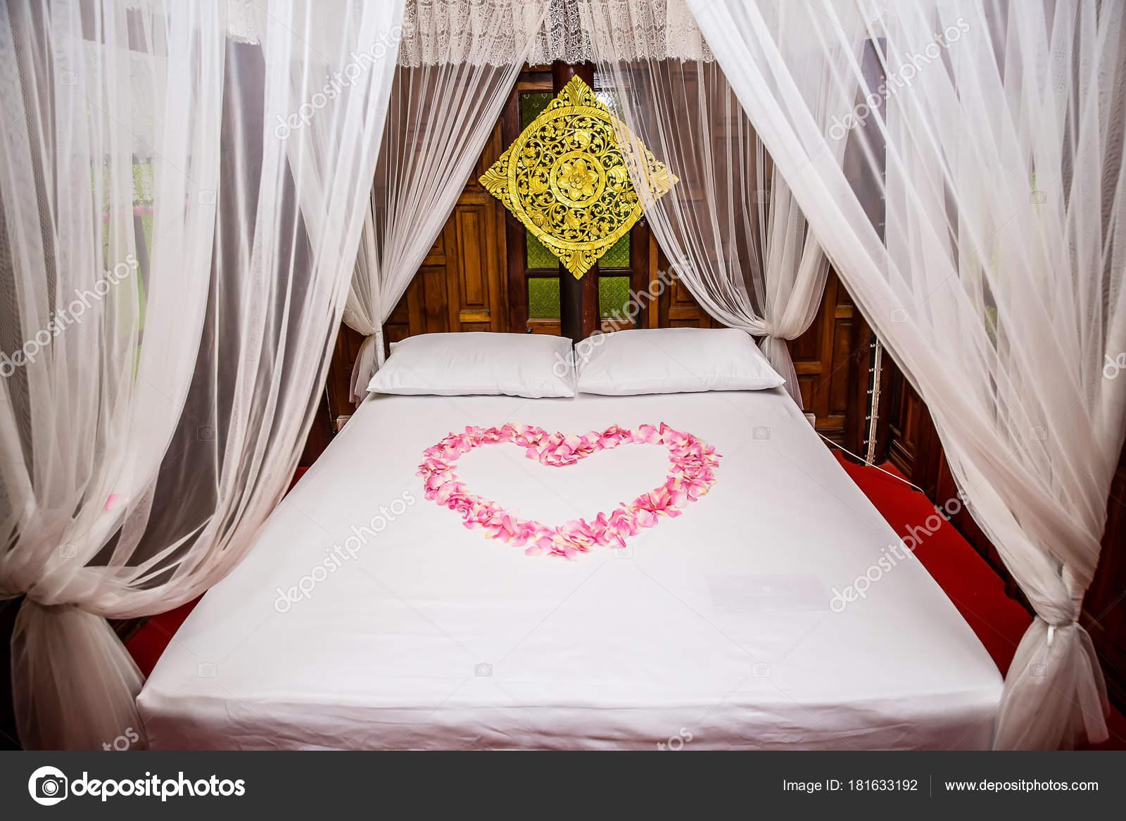 Camere Da Letto Romantiche Con Petali Di Rosa : Forma cuore rosa petali rosa sul letto bianco decorazione della