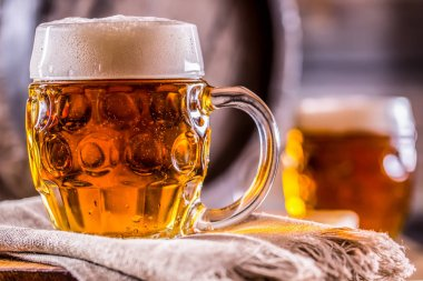Beer. Two cold beers. Draft beer. Draft ale. Golden beer. Golden ale. Two gold beer with froth on top. Draft cold beer in glass jars in home pub hotel or restaurant. Empty beer glass. Still life