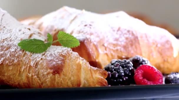 Křupavé čerstvé croissanty maliny ostružinové borůvky a melissa posypané práškovým cukrem podávaným v kavárně. Video záběr 4k 50fps.