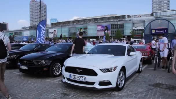 Lidé chodí kolem autosalonu Ford. Mustang moc