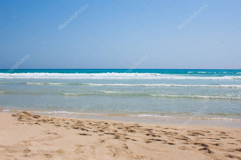 Blue sea with white waves and sand with footprints