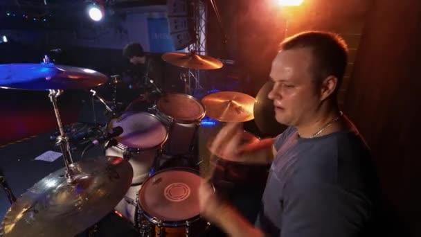 Moskva, Rusko - 21. ledna 2018: Koncert rockové kapely na scéně. Bubeník, kytarista
