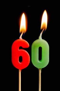 Burning candles in the form of sixty figures (numbers, dates) for cake isolated on black background. The concept of celebrating a birthday, anniversary, important date, holiday, table setting, cake de