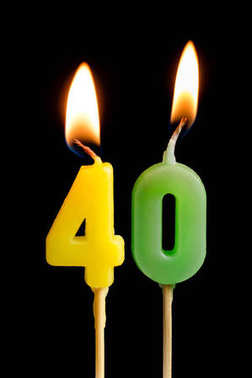 Burning candles in the form of forty figures (numbers, dates) for cake isolated on black background. The concept of celebrating a birthday, anniversary, important date, holiday, table setting, cake de