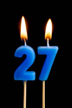 Burning candles in the form of 27 twenty seven (numbers, dates) for cake isolated on black background. The concept of celebrating a birthday, anniversary, important date, holiday, table setting