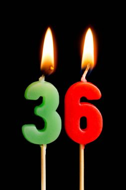 Burning candles in the form of 36 thirty six (numbers, dates) for cake isolated on black background. The concept of celebrating a birthday, anniversary, important date, holiday, table setting