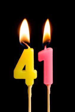 Burning candles in the form of 41 forty one (numbers, dates) for cake isolated on black background. The concept of celebrating a birthday, anniversary, important date, holiday, table setting