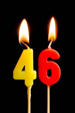 Burning candles in the form of 46 forty six (numbers, dates) for cake isolated on black background. The concept of celebrating a birthday, anniversary, important date, holiday, table setting