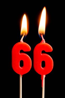 Burning candles in the form of 66 sixty six (numbers, dates) for cake isolated on black background. The concept of celebrating a birthday, anniversary, important date, holiday, table setting