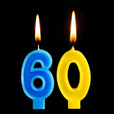 Burning birthday candles in the form of 60 sixty figures for cake isolated on black background. The concept of celebrating a birthday, anniversary, important date, holiday, table setting
