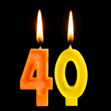 Burning birthday candles in the form of 40 forty figures for cake isolated on black background. The concept of celebrating a birthday, anniversary, important date, holiday