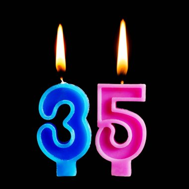 Burning birthday candles in the form of 35 thirty five figures for cake isolated on black background. The concept of celebrating a birthday, anniversary, important date, holiday