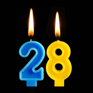 Burning birthday candles in the form of 28 twenty eight for cake isolated on black background. The concept of celebrating a birthday, anniversary, important date, holiday