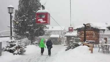 two people walking in the pedestrian zone under a heavy snowfall in a winter afternoon