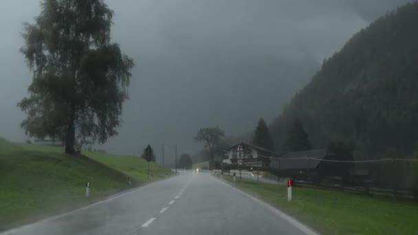 Horská silnice pod haldami v letní odpoledne s automobily a jezdce na protilehlém pruhu