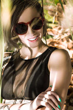 Beautiful young woman in sunglasses smiling at camera under palm tree stock vector