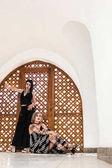 Fotografie krásné stylové dívky při pohledu na fotoaparát a pózování poblíž dekorativní dřevěné brány v Egyptě