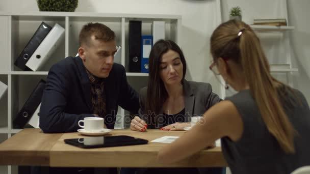 Podepsání smlouvy při sezení spolu se svou ženou v real realitní kancelář veselý mladý muž. Rodina žádající o hypotéku kupovat ubytování během setkání s realitní agent v úřadu