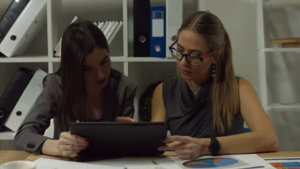 Busy female coworkers working on digital tablet
