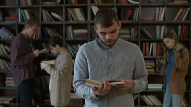 Hezký bokovky student čtení knihy v knihovně