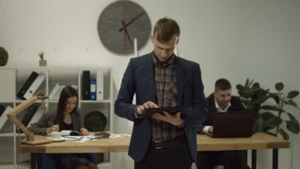 Pohledný podnikatel s digitálním tabletu v úřadu