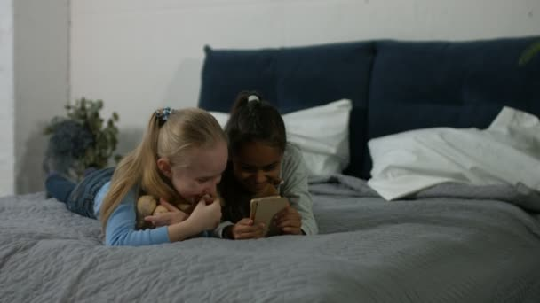 Nadšený multi etnické děti sledovat video v telefonu