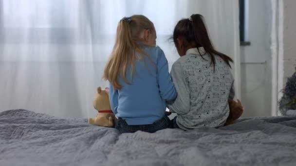 Multi etnické holčičky sedící na posteli – pohled zezadu