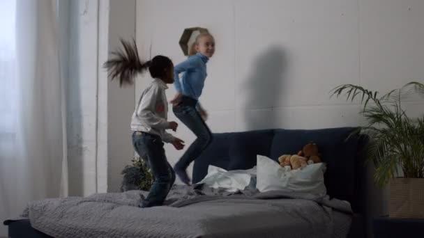 Pozitív multi etnikai gyerekek ugrás az ágyon