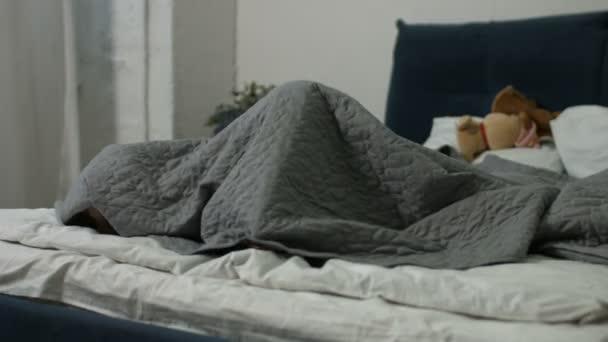 Vidám lány néz ki a takaró alatt